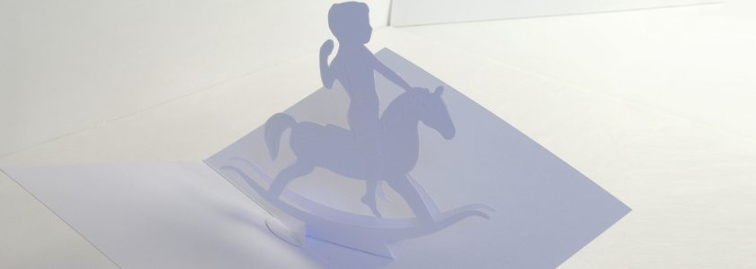 Paper pop-up card of child on a rocking horse